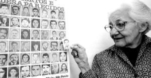 helena-dos-santos-pereira-presidente-do-movimento-tortura-nunca-mais-e-mae-de-miguel-dos-santos-pereira-preso-politico-desaparecido-segura-cartaz-com-fotos-de-mortos-e-desaparecidos-1394549843360_956x500